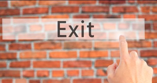 Exit - Hand pressing a button on blurred background concept on v